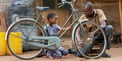 A father and son work together to repair a bicycle