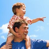 Um pai com o filho nos ombros apontando para alguma criação de Deus
