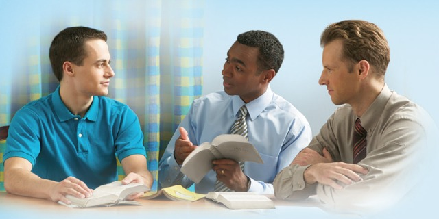 Two of Jehovah's Witnesses studying the Bible with a man
