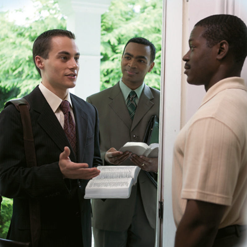 A Bible student shares a Bible message with a man as his teacher looks on