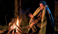 A man warms himself by a fire