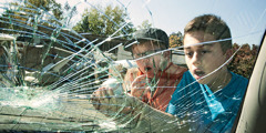 Two boys look at a broken car windshield