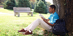 A young man sits outside and reads the Bible