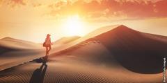 A person walks across a desert