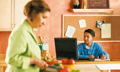A boy uses the Internet in the kitchen, while his mother prepares food