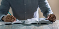 A man studies the Bible using the book How to Remain in God's Love