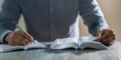 Un homme étudie la Bible à l'aide du livre Restez dans l'amour de Dieu