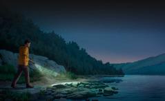 Un bărbat care se plimbă seara pe malul stâncos al unui lac, având în mână o lanternă care îi luminează calea