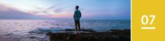Lección 7. Unhombre de pie en unas rocas junto al mar mirando al horizonte después de la puesta del sol.