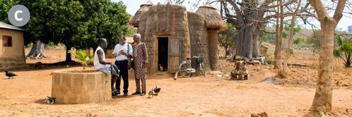 C. Kaksi Jehovan todistajaa kertoo hyvää uutista miehelle pienessä kylässä Beninissä.