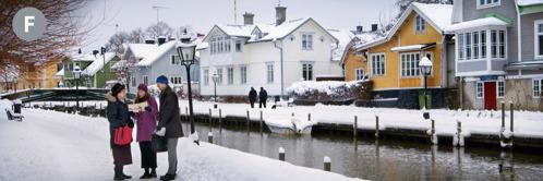 F. Kaksi Jehovan todistajaa kertoo hyvää uutista naiselle lumisella jalkakäytävällä kanavan varrella Ruotsissa.