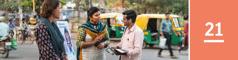 Lección 21. Unhombre en la calle de una ciudad hablando con dos testigos de Jehová que están junto a un exhibidor de publicaciones.