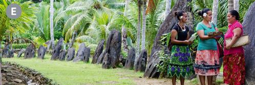 E. Dve Jehovove svedkyne zvestujú dobrú správu žene, ktorá stojí pri veľkých kamenných kotúčoch na ostrove Yap