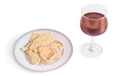 Un plato con pan sin levadura y una copa de vino.