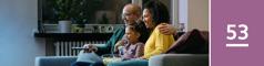 Oppijakso 53. Isä, äiti ja pieni tyttö syövät popcornia ja katsovat televisiota.