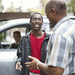 A father giving his teenage son the car keys
