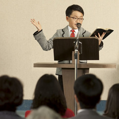 A boy giving a Bible talk at a meeting