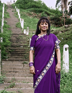Nalini by the 125 steps leading to her home