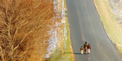 A mother and her two children walking down a road toward an unseen destination