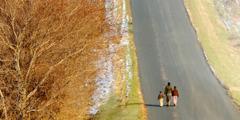 En mor og hennes to barn går bortover en vei mot et ukjent bestemmelsessted