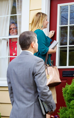 From her window, a woman observes Jehovah's Witnesses knocking on her door