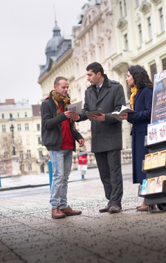 Jehovah's Witnesses in a metropolitan area share Bible information with a man