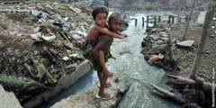 Children play near extremely polluted land and water