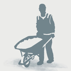 A Kingdom Hall construction servant pushes a wheelbarrow