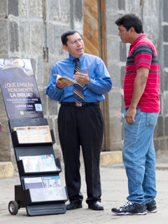 One of Jehovah's Witnesses sharing in public witnessing using a literature cart