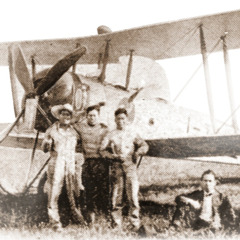 Christian brothers in front of an airplane that was used to scatter invitations