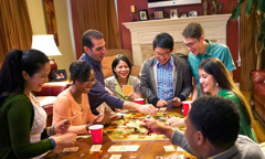 Young Christians having a good time as they play a board game