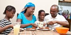 Муж и жена уживају у оброку са своје две ћерке