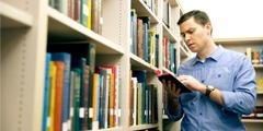 Човек чита Свето писмо у библиотеци