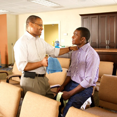 At the Kingdom Hall, an elder explains to a young brother why a task needs to be done