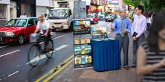 Un anciano ta siña un sirbidor ministerial predica cu stand di literatura den un caya hopi druk, conoci como Haiphong Road, na Kowloon, Hong Kong