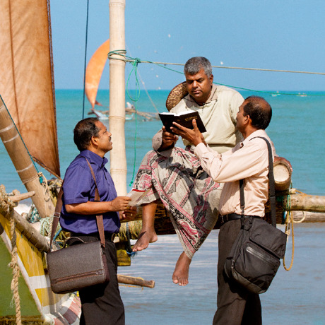 Two of Jehovah's Witnesses preaching by the seashore; they share a Bible text with a man