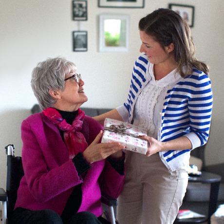 Wanita lansia memberikan hadiah kepada temannya