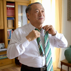 An older man putting on a tie