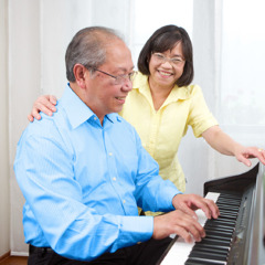 An older man enjoys playing the piano for his wife