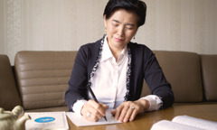 An older woman writing a letter