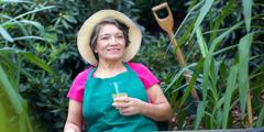 En eldre kvinne tar en pause i hagearbeidet