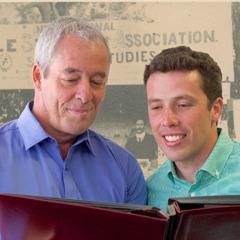 Far og søn kigger på gamle familiebilleder