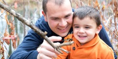 A father and son looking at a dragonfly