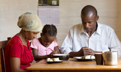 A man prays with his wife and daughter over a simple meal