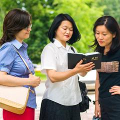 Masako och en annan syster visar ett bibelställe för en kvinna.