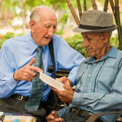 Parke ant suoliuko senyvas brolis kalbasi su kitu vyru apie Bibliją