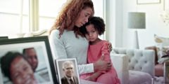 A woman and a little girl sit beside photos of loved ones, hold each other, and grieve together