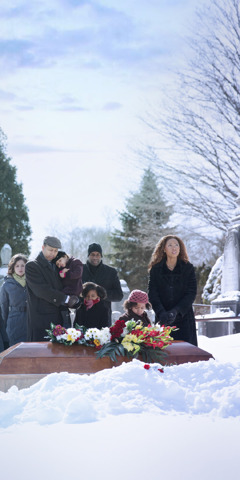 Adults and children gather around a casket at a cemetery
