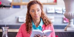 Eine Frau mit einer geöffneten Bibel in der Hand; sie strahlt Zuversicht aus