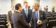 Jehovah's Witnesses of various races greet one another in a Kingdom Hall